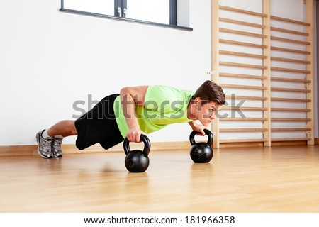 Young sportsman doing push-ups on kettlebell