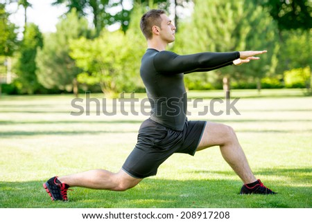 Young sportsman doing stretching exercise in the park at sunny day