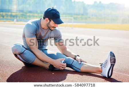 Young sportsman doing stretching exercise, preparing for morning training in the park.