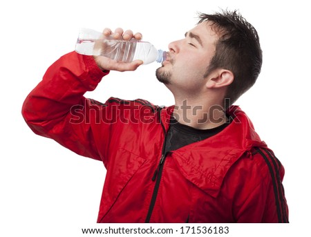 Young sportsman drinking water on white background