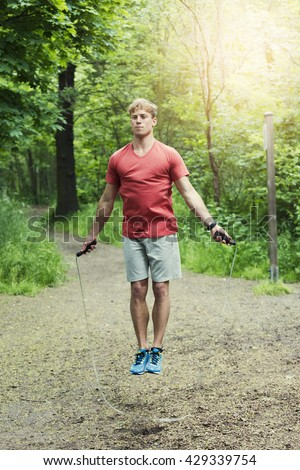 Young sportsman exercising jumping rope. Forest background