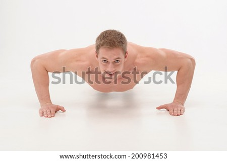 Young sportsman, fitness muscle model guy making push ups exercise isolated on white. Concept of sport, keeping fit