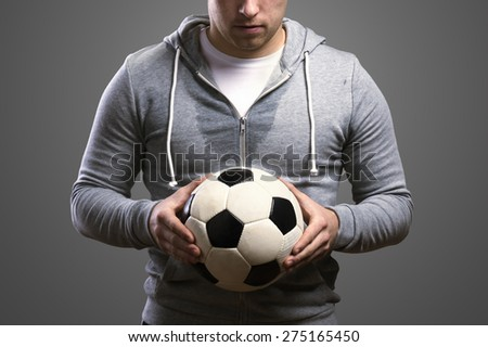 Young sportsman holding a soccer ball. Studio shot on gray background. - stock photo