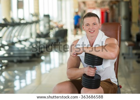 Young sportsman in gym. Guy with towel on the neck in gym. Apparatus in gym on background.  - stock photo
