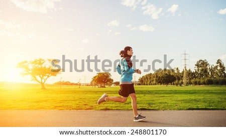 young sportsman jogging in the beautiful sunset - stock photo