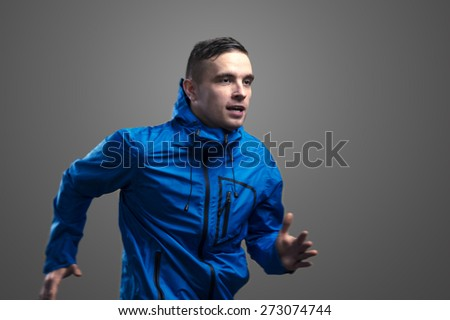 Young sportsman jogging. Studio shot on gray background. - stock photo