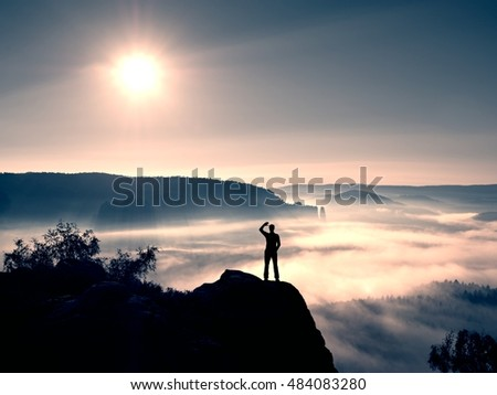 Young sportsman shadowing his eyes from the bright light of the daybreak Sun. Colorful misty morning in rocks.