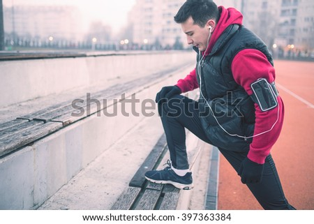 Young sportsman working-out in a park, stretching hamstrings before running. Selective focus, depth of field - stock photo
