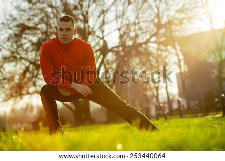 Young sportsman working-out in a park, stretching out before running - stock photo
