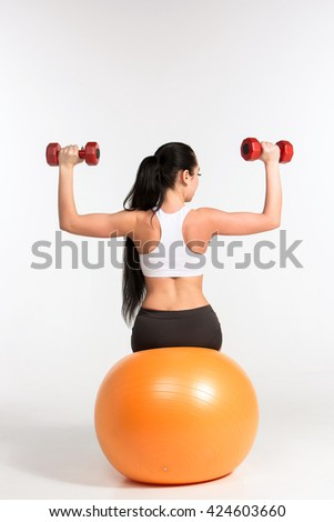 Young sportswoman doing fitness exercise with dumbbells on pilat