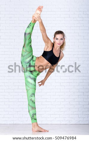 Young sportswoman stretching in the studio