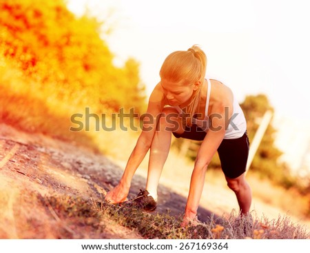Young sportswoman stretching legs before sprint start. Energetic female jogger ready to run on forest trail.   - stock photo