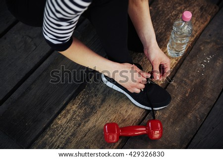 Young sportswoman tying laces on her sneakers ready for jogging and training. Concept of healthy lifestyle, sport and diet.