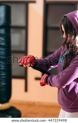 Young sportswoman wrapping hands near punching bag. Sporty girl in sport wear at gym wrapping her hands with red boxing wraps. Ready for exercises or training with punching bag female kickboxer - stock photo