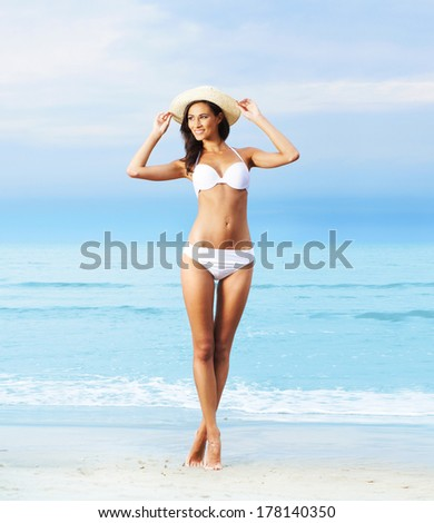 Young, sporty and happy woman posing on the beach - stock photo