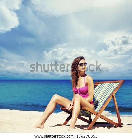 Young, sporty, beautiful and happy woman relaxing on a summer beach