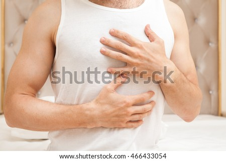 Young sporty Caucasian man in white shirt with hands on chest