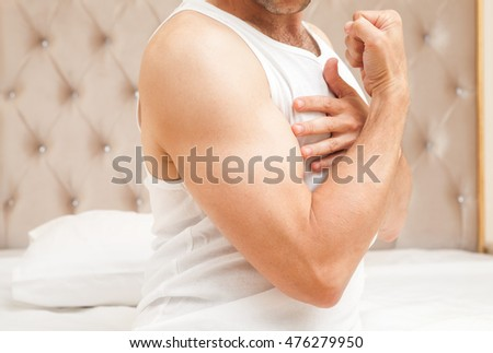 Young sporty Caucasian man torso in white shirt shows his biceps in bedroom