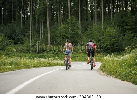 Young sporty couple riding on mountain bicycle on the forest road. Back view. - stock photo