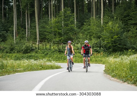 Young sporty couple riding on mountain bicycle on the forest road. Front view. - stock photo