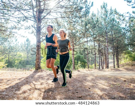 young sporty couple running in the forest