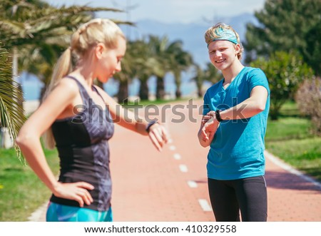 Young sporty couple starting their timer before jogging - stock photo
