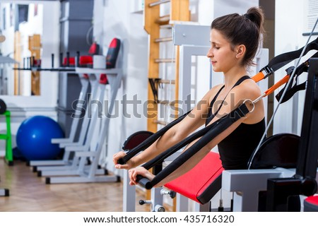 Young, sporty, female, athlete girl , training her chest muscles with TRX suspension strap at the gym. - stock photo