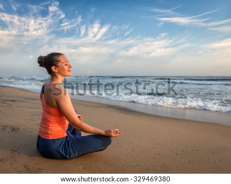 Young sporty fit woman doing yoga - meditating and relaxing in Padmasana Lotus Pose)  position asana with chin mudra outdoors at tropical beach on sunset - stock photo