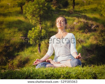 Young sporty fit woman doing yoga outdoors - meditating and relaxing in Padmasana Lotus Pose) with chin mudra on green grass in forest. Vintage retro effect filtered hipster style image.