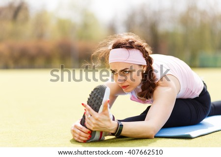 Young sporty girl doing stretching on fitness mat. Attractive sportswoman stretching at the outdoors