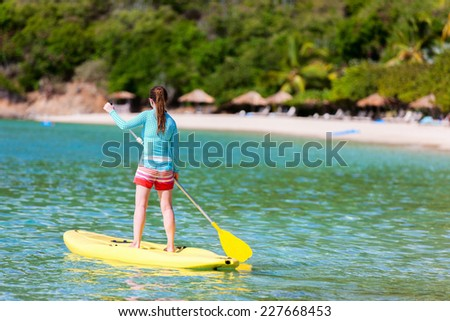 Young sporty girl on tropical beach vacation paddling on stand up board