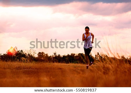 Young sporty girl running on a rural road .