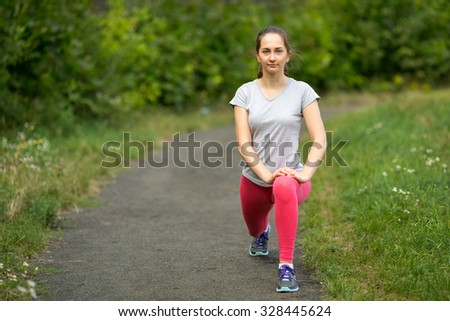 Young sporty girl warming up before Jogging in the Park.