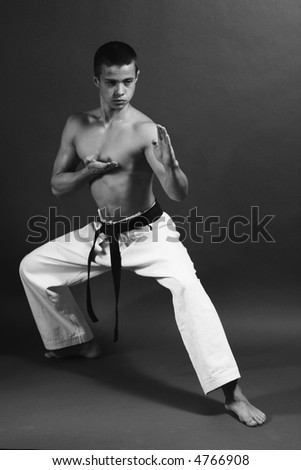 Young sporty karate man doing special exercise. B&W - stock photo