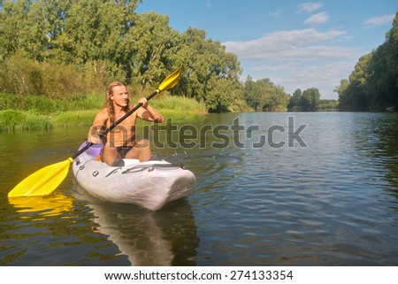 Young sporty man kayaks on misty river. Shot near Bonnievale, Western Cape, South Africa. - stock photo