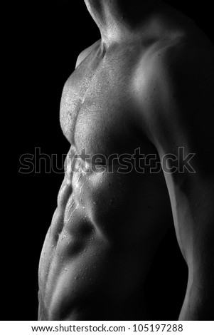 Young sporty man with waterdrops on skin over black background - stock photo
