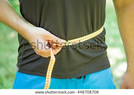 Young sporty man with with measuring tape outdoor.Close up, concept of healthy and sport - stock photo