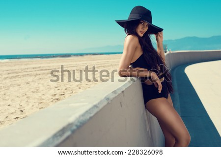 Young, sporty, sexy and beautiful girl in swimsuit resting on exotic beach in summer. Lifeguard tower. - stock photo