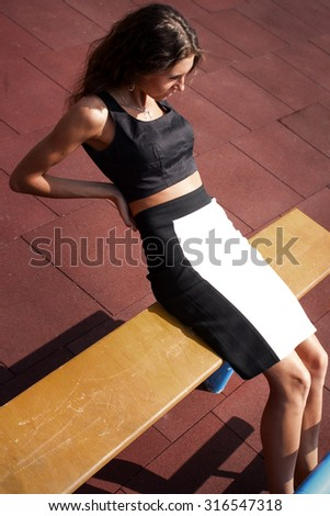 Young sporty teenage model pumps and crunches the abdominals and posing on playground near horizontal and parallel bars, stairs, wearing black and white top and skirt - stock photo
