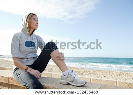 Young sporty thoughtful woman sitting by the sea, having a break from exercising during a sunny morning with a blue sky. - stock photo