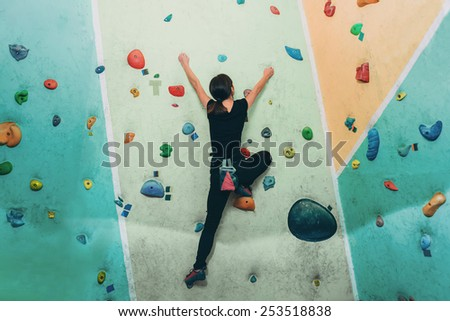 Young sporty woman climbing up on practice rock wall in gym, rear view - stock photo