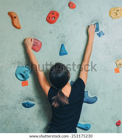 Young sporty woman climbing up on rock wall in gym, rear view - stock photo