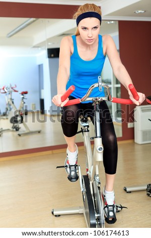 Young sporty woman doing exercise on bicycle in the gym centre.