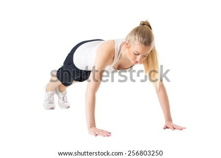 Young sporty woman doing push-ups and exercising - stock photo