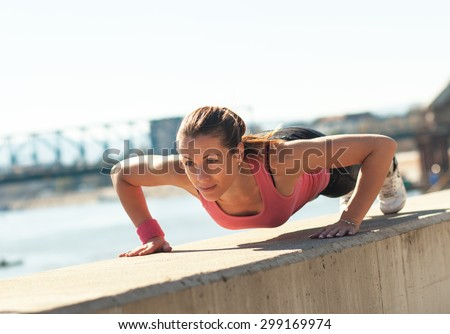 Young sporty woman doing push-ups in sunny day on riverbank. - stock photo
