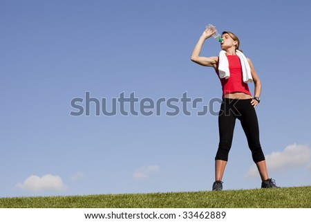 young sporty woman drinking water from a bottle in a park