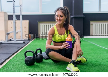 young sporty woman drinking water in gym, holding bottle,  having break - stock photo