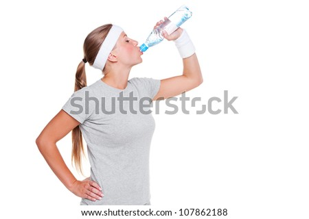 young sporty woman in grey t-shirt drinking water over white background - stock photo