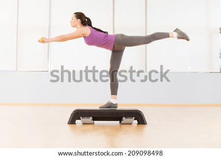 young sporty woman in gym centre. pretty girl doing exercise on step - stock photo