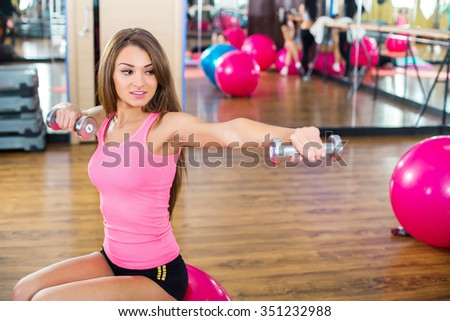 Young sporty woman in gym doing fitness exercice with pink ball - stock photo